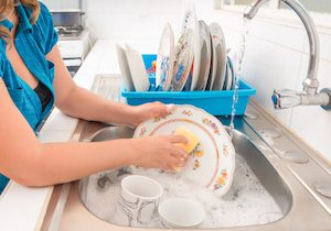 Washing the dishes in the kitchen sink