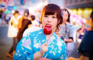 りんご飴を食べる女性