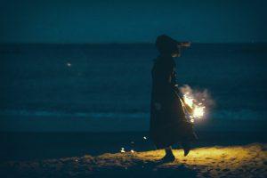 夜の浜辺で手持ち花火と女性のシルエット