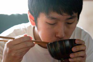 味噌汁を飲む男