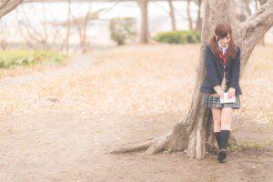 木陰で待つ女子高生