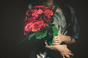 バラの花束をを抱えた女性