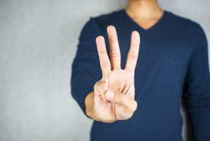 3つの指を立てる男性