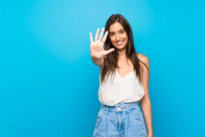 5本の指を立てる女性
