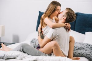 man-kissing-woman-sitting-on-bed_23-2148027335